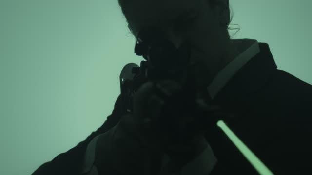 アサルトライフルを狙うボディガードをクローズアップ。 - こっそり点の映像素材/bロール