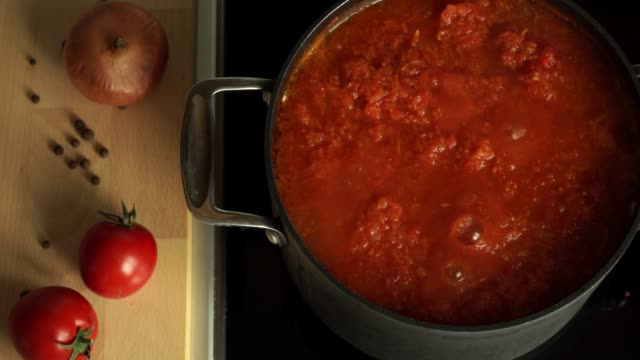 vídeos de stock e filmes b-roll de close up of boiling hot tomato sauce cook on stove in saucepan, on background of wooden cutting board with fresh red tomatoes, onions and pepper. italian pasta and pizza sauce. - sauce tomatoes