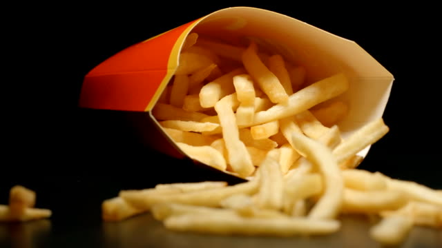 slow motion: close up of box with french fries falls on a table - junk food stock videos and b-roll footage