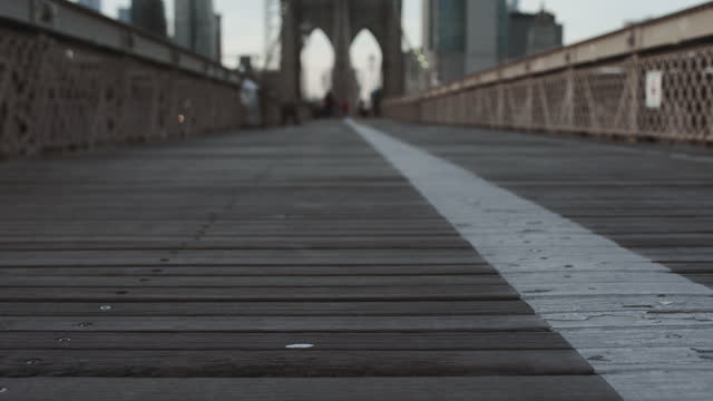 Close up of Brooklyn Bridge footpath A low angle shot shows the narrow, wooden boards of the Brooklyn Bridge walkway. new york architecture stock videos & royalty-free footage