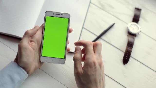 nahaufnahme der geschäftsmann hände mit mobiltelefon mit greenscreen für internet und e-mail. - schriftrolle stock-videos und b-roll-filmmaterial