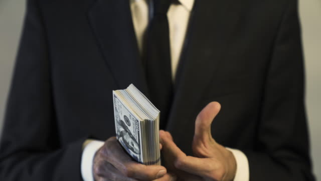 Close up of Businessman Holding a Big Stack Bundle of $100 Bills Money in Hands