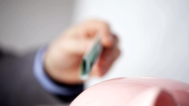 close up of businessman putting european money into piggy bank