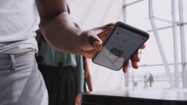 stockvideo's en b-roll-footage met close-up van zakenman met behulp van mobiele telefoon met elektronische instapkaart op het scherm dat hij scant als hij boards aircraft-shot in slow motion - vliegveld vertrekhal