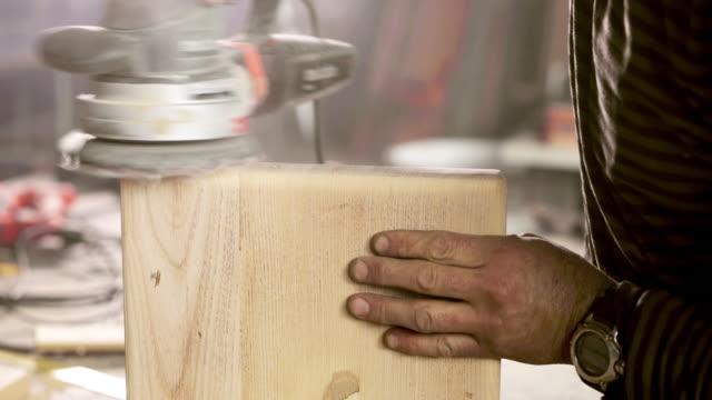 Gros plan du charpentier, polissage de pièce de bois avec la ponceuse. - Vidéo