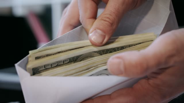 Close up of cash money in envelope in hands. Money bonus in paper envelope