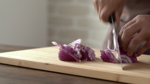 Close up of chef hands slicing red onion with knife on wooden cutting boarding in kitchen preparing for cooking ingredient