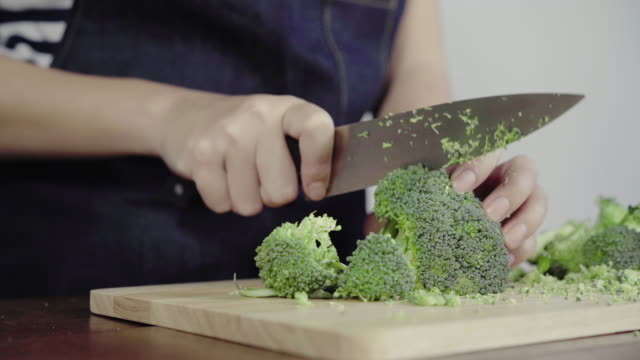vídeos de stock e filmes b-roll de close up of chief woman making salad healthy food and chopping broccoli on cutting board. - brócolo
