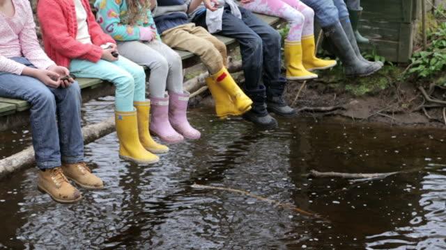 Close Up Of Children's Feet Dangling From Wooden Bridge video