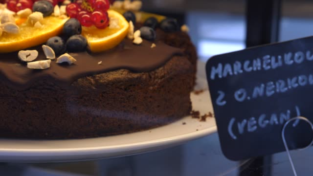 Close up of chocolate carrot vegan cake decorated with fruits and berries on a display in bakery