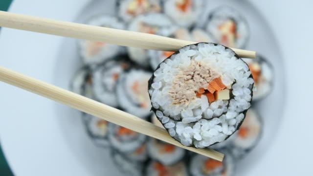 Close up of chopsticks holds sushi maki gunkan roll over a plate video
