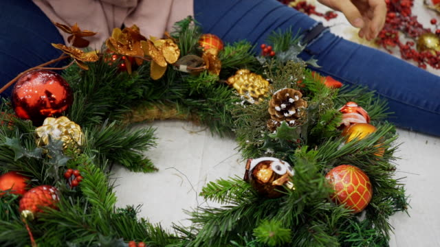 close up of christmas wreath is being decorated by female designer - ghirlanda decorazione video stock e b–roll