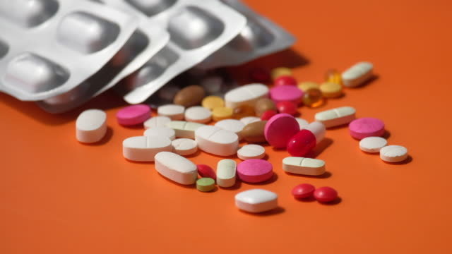 close up of colorful pills spilling on dray desk - antidolorifico video stock e b–roll