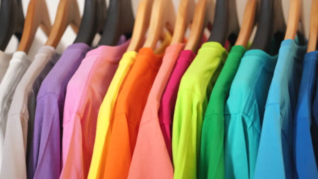 close up of colorful t-shirts on hangers, apparel background - вешалка стоковые видео и кадры b-roll