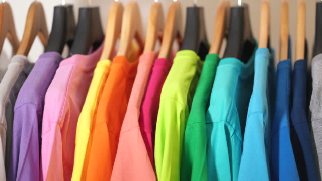 Close up of Colorful t-shirts on hangers, apparel background Close up of Colorful t-shirts on hangers, apparel background rack stock videos & royalty-free footage