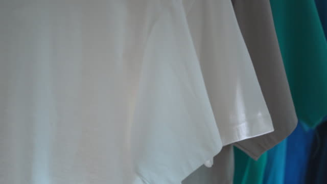 Close up of Colorful t-shirts on hangers, apparel background Close up of Colorful t-shirts on hangers, apparel background coathanger stock videos & royalty-free footage