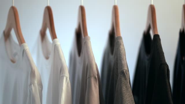 vídeos de stock e filmes b-roll de close up of colorful t-shirts on hangers, apparel background - teeshirt template