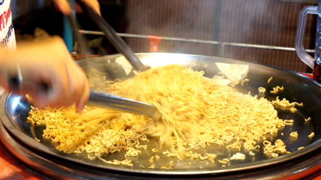 Close up of cooking instant noodles in frying pan video