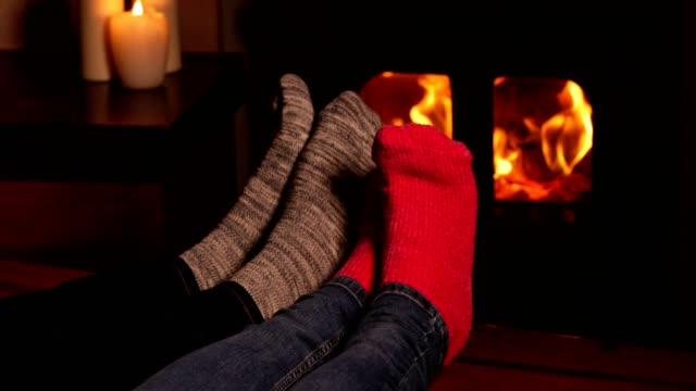 close up of cosy couple at home wearing socks warming feet by flames of wood burning stove fire - calzino video stock e b–roll