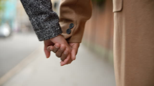 Close Up Of Couple Holding Hands Walking Along City Street