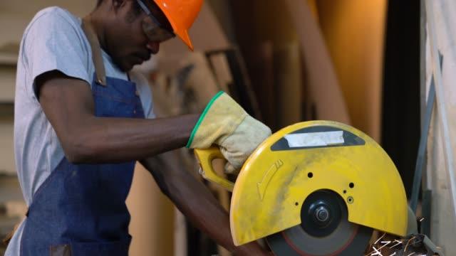 nahaufnahme des handwerkers in seiner werkstatt schneiden einer metallstange mit einer kreissäge - kreissäge stock-videos und b-roll-filmmaterial