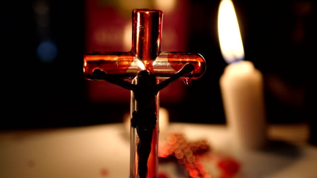 Close up of cross of jesus lit by candle video
