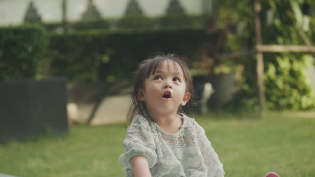 Close up of Cute Asian girl is talking to her parent beside her brother at the garden video