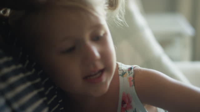 Close up of cute little blonde girl snuggling and asking questions as father reads to her Close up of cute little blonde girl snuggling and asking questions as father reads to her pigtails stock videos & royalty-free footage