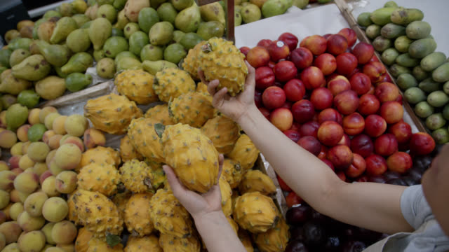 Close up of delicious colorful fruits at a farmers market and unrecognizable woman grabbing two dragonfruits - lifestyles
