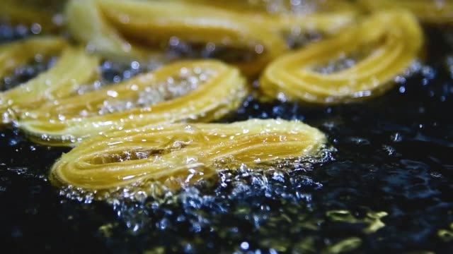 Close up of delicious looking golden churros being fried in boiling oil in slow motion. Tasty food and cooking concept.