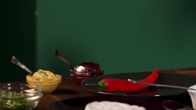 緑の壁の背景に木製のテーブルの上に立って調理のための異なる成分のクローズアップ。ストック映像。唐辛子、クランベリー、マヨネーズ、マスタードソース、カマンベールチーズ、緑 ビデオ