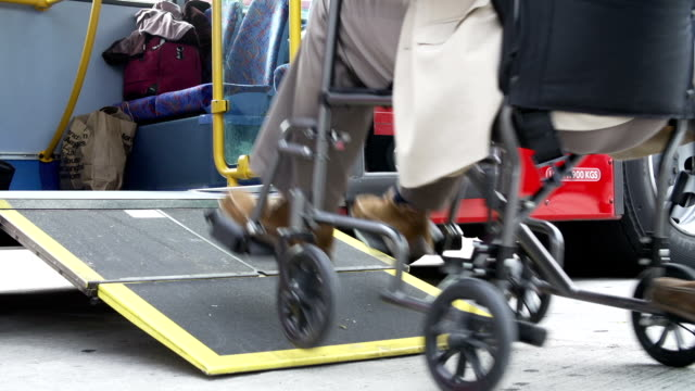 Close Up Of Disabled Person In Wheelchair Boarding Bus Close up of disabled passenger in wheelchair being pushed onto bus.Shot on Sony FS700 in PAL format at a frame rate of 25fps disability stock videos & royalty-free footage