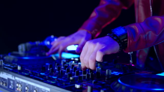close up of dj mixer controller desk in night club disco party. dj hands touching buttons and sliders playing electronic music . amazing close up of dj hands mixing and scratching music on vinyl plate . - ibiza filmów i materiałów b-roll