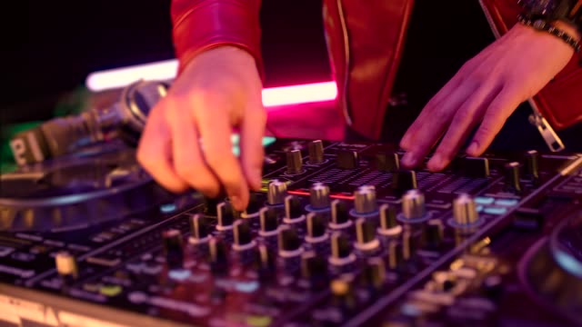 vídeos de stock e filmes b-roll de close up of dj mixer controller desk in night club disco party. dj hands touching buttons and sliders playing electronic music . amazing close up of dj hands mixing and scratching music on vinyl plate . - led painel