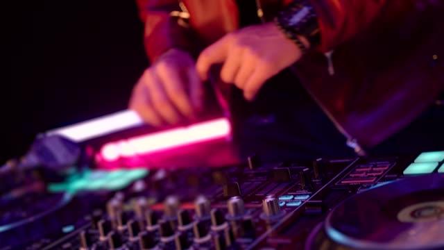 Close Up von Dj Mixer Controller Desk in Night Club Disco Party. DJ Hands berühren Tasten und Slider Spielen elektronische Musik . Erstaunliche Nahaufnahme von DJ Hands Mixing und Scratching Musik auf Vinyl Plate. – Video