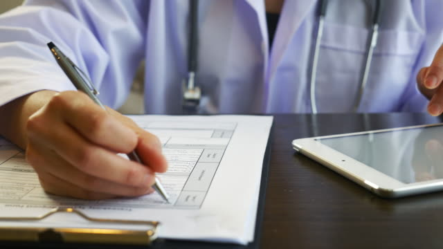 close up of doctor's hands writing on medical chart - promemoria video stock e b–roll