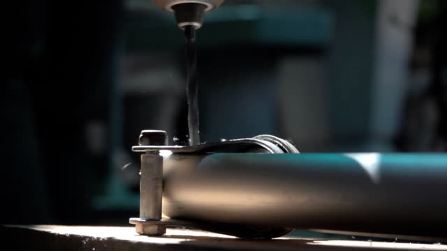 close up of drilling a hole in steel, slow motion - truciolo video stock e b–roll