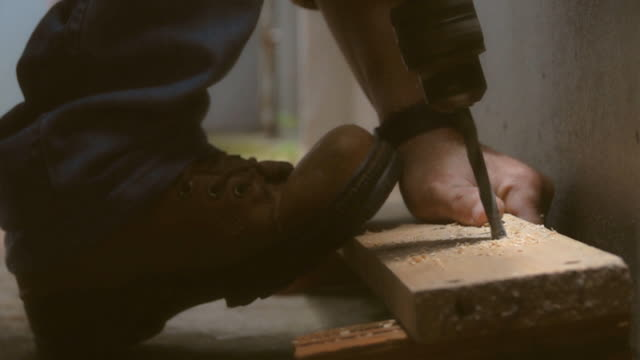 Close Up of drilling a hole in wooden plank, slow motion