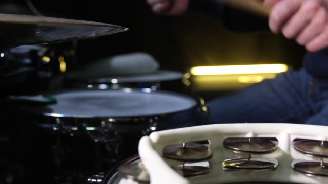 Close up of drum tambourine and a drummer playing on drums on background. Slider shot. video