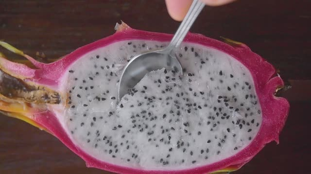 close up of eating fresh dragon fruit for dessert on wooden table in slow motion. hd, 1920x1080 - pitaja filmów i materiałów b-roll