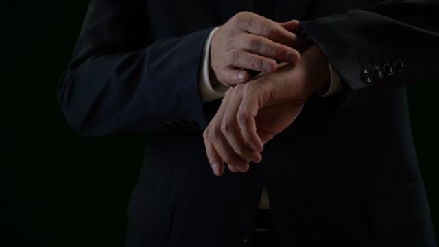 Close up of elegant business man in suit straightening sleeves of shirt Close up of elegant business man in suit straightening sleeves of shirt. Professional businessman checking time, cropped view in low key sleeve stock videos & royalty-free footage
