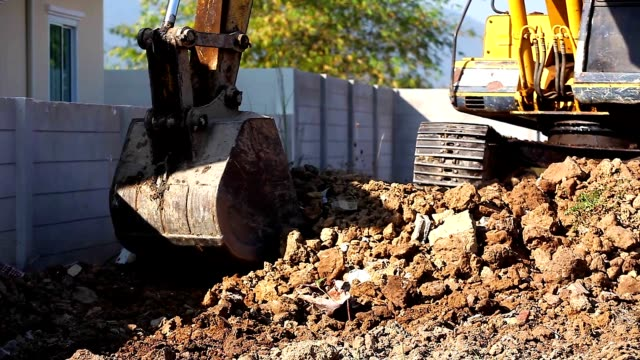 close up of excavator backhoe with shovel between working at construction and clearing at construction outdoor. - ghiaia video stock e b–roll
