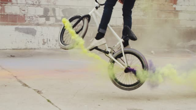 Close up of extreme BMX biker doing tail whip trick with purple and yellow colored smoke grenade  in urban environment