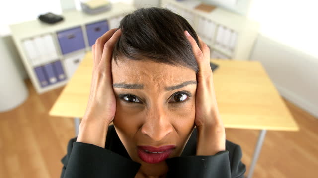 Close up of extremely frustrated business woman screaming at work video