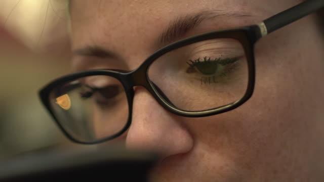 stockvideo's en b-roll-footage met close-up van de ogen van aantrekkelijke coole roodharige vrouw met glazen reflectie, sproeten en rood haar kijken naar internet video op smartphone zittend op de bushalte in de straat, met vage telefoon op de voorgrond. - bril brillen en lenzen