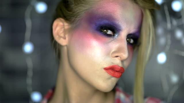 クローズアップの顔にマルチカラーのメイクアップ - アイシャドウ点の映像素材/bロール