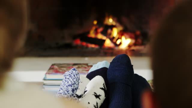 närbild av familjen värmande fötter av öppen eld - sitta bildbanksvideor och videomaterial från bakom kulisserna