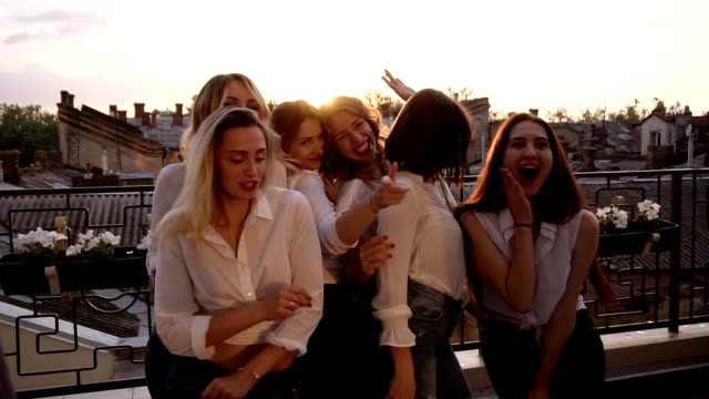 close up of fashionable girls in the same casual clothes seductively dancing, posing in front of the camera on the terrace. evening dusk - bachelorette party stock videos and b-roll footage