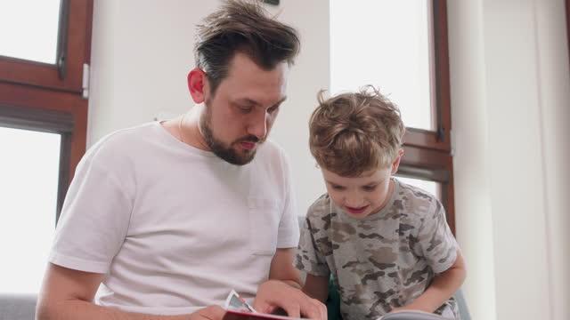 da vicino padre e figlio trascorrono del tempo insieme a casa leggendo un libro sul divano e componendo una storia dalle immagini in esso. il muro e la finestra sono in background - padre single video stock e b–roll