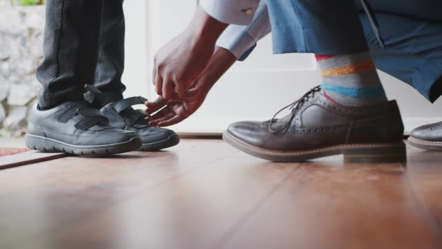 close up of father wearing shirt and tie, brogue shoes and striped socks kneeling down on one knee to fasten the straps on his sonís shoes before school, low section, close up of feet - отъезд стоковые видео и кадры b-roll